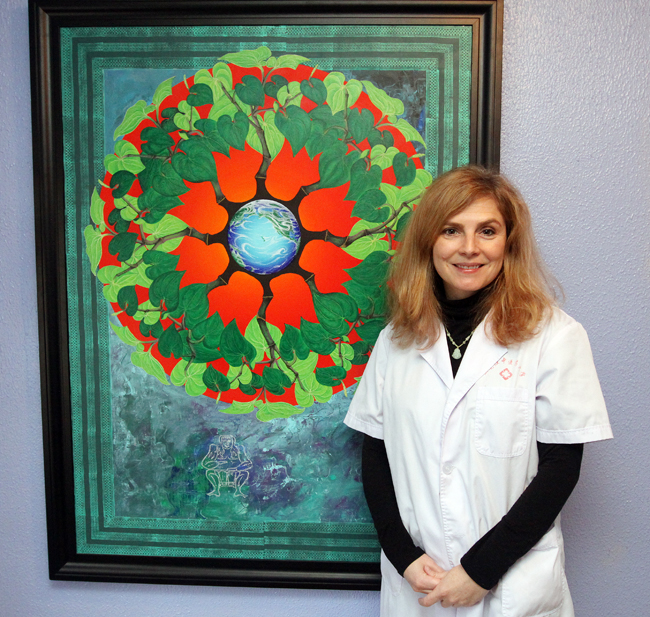 Karena Luttmer, owner of Thrive Acupuncture, stands in front of a painting made by a family member. (Tyler Cobb / Park Record)