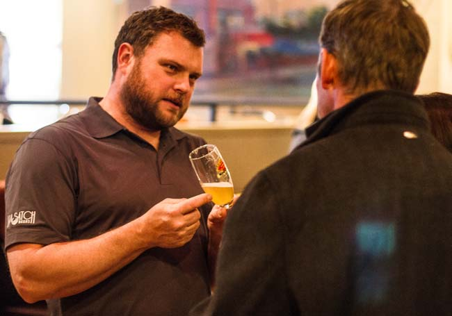 Adam Curfew, director of cellar operations for Wasatch Brew Pub, reveals some of the ingredients in his signature brew, Ghostrider, and how he decided the alcohol content level to Mark Kennedy Wednesday at the Wasatch Ghostrider White IPA release party. Christopher Reeves/The Park Record.