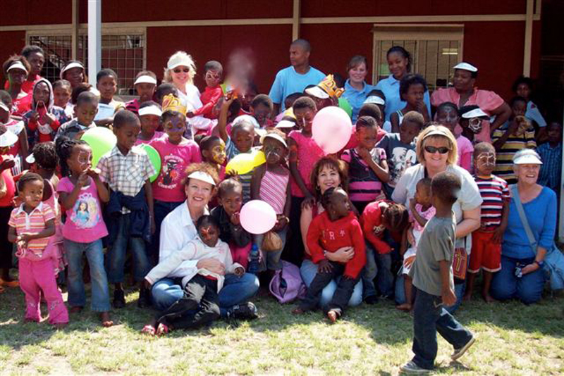 Volunteers for U-SA Cares for Life are shown here with a group of South African children. The nonprofit organization is holding a charity boutique fundraiser at Little Miner's Montessori School on June 1. The money raised will help impoverished, disease-strickened and orphaned children in South Africa. (Photo courtesy of Rose Pylidis)