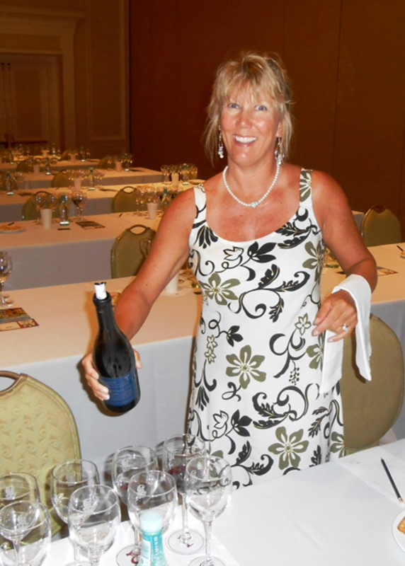 Pamela Wood, president and founder of the Park City Wine Club, prepares to pour wine during an event in Hawaii last June. Wood, a certified sommelier, is excited about the rising popularity of the club in Park City. (Photo courtesy of Pamela Wood)