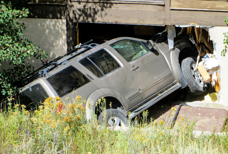 A sport utility vehicle came to rest in a leaning position after crashing into a condominium. Jay Hamburger/Park Record