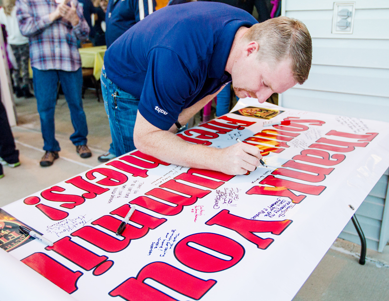 (Left to right) Kevin Eder, Iva Eder, Savannah Varner and Andy Varner sign a banner showing their appreciation to the South Summit firefighters during a dinner Thursday, Sept. 19, at the North Summit Fire District firehouse for their efforts during the recent Rockport fire. (Christopher Reeves/The Park Record)
