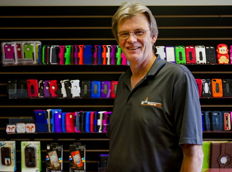 Brad Casper, owner of Dr. Phone Fix, stands in his store among all of the colorful accessories his store has to offer. Christopher Reeves/Park Record.