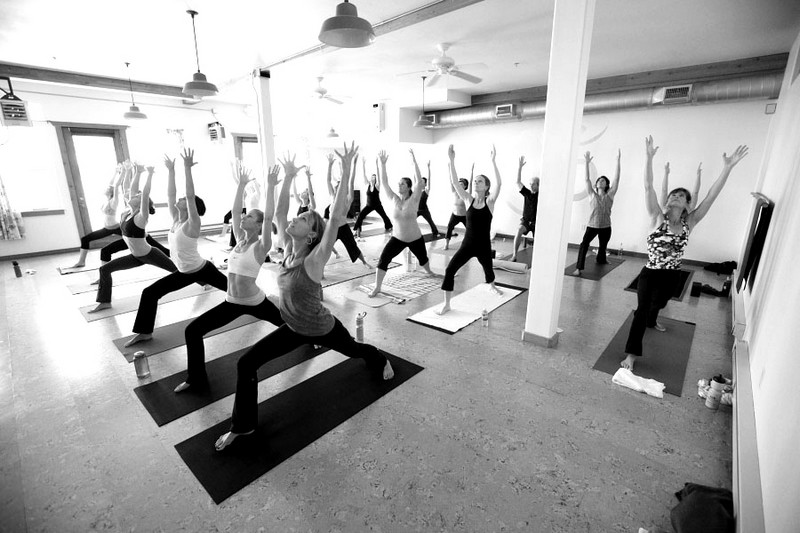 Clients practice the Crescent Lunge at Tadasana Yoga Studio at its current location at 2700 West Homestead Rd. The studio will relocate in January to Quarry Village. Photo courtesy of Melissa Garland.