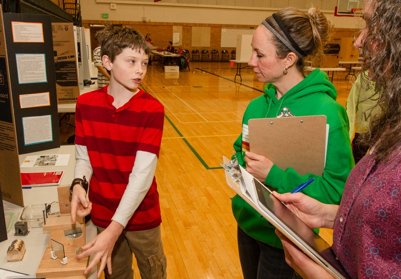 Alex Prucka, left, a seventh-grader at Ecker Hill Middle School, explains his science project using holography as a data storage technique to judges Rebecca Hill, center, and Danielle Montague-Judd during the Park City School District Science Fair Tuesday, Feb. 25, at Treasure Mountain Junior High School. Christopher Reeves/Park Record.