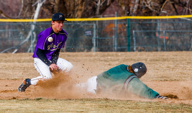 Carson RichIns (left) of the North Summit Braves gets the ball knocked loose as South Summit's Daxton Hansen slides safely into second base during their rivalry game in Kamas Tuesday. (Photo by: Christopher Reeves/The Park Record)
