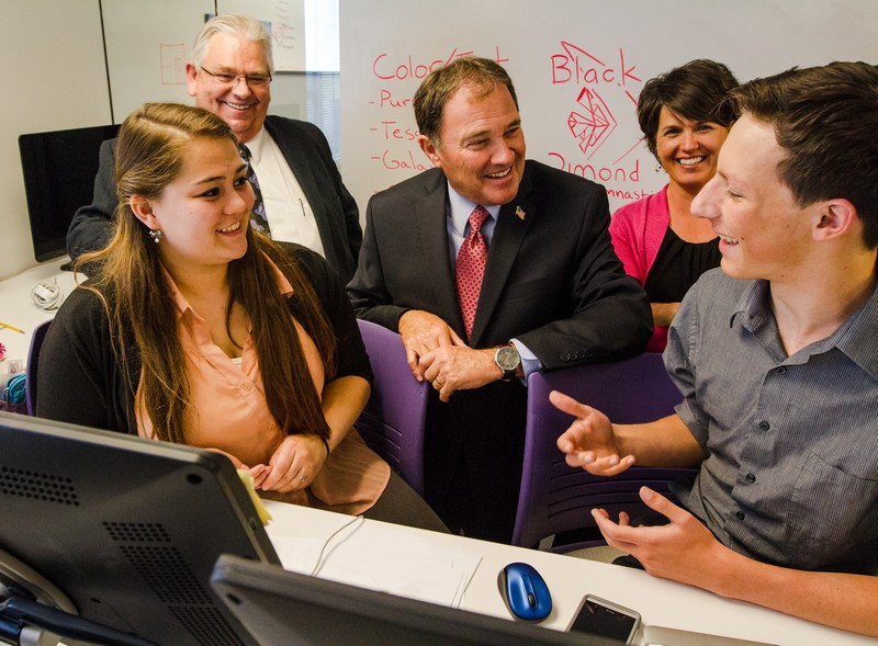 Cara Christensen, far left, and her project partner Mitchell Elliott speak with Utah Sen. Kevin Van Tassell, Gov. Gary R. Herbert and educational advisor Tami Pyfer about their graphic design project for Black Diamond Gymnastics on Thursday, May 15. (Christopher Reeves/Park Record)
