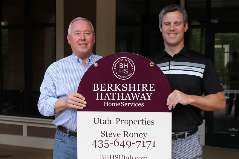 Berkshire Hathaway HomeServices Utah Properties Chairman and CEO Stephen Roney, left, and his son and Senior Vice President Thomas B. Roney display one of the new signs that has replaced Prudential Utah Real Estate signs throughout town. Alexandria Gonzalez/Park Record.