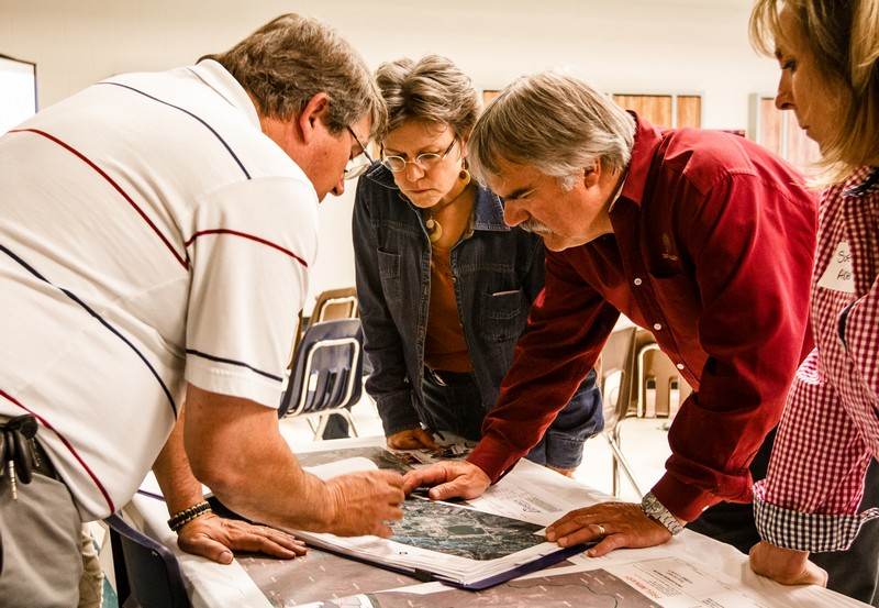 Bob Wheaton, a landowner in the Woodland area, right, and Lisa Yoder, who is Summit County's sustainability coordinator, study maps showing a broad proposed route of a Tesoro pipeline with Scot Cheney during an event on Tuesday. (Christopher Reeves/Park Record)