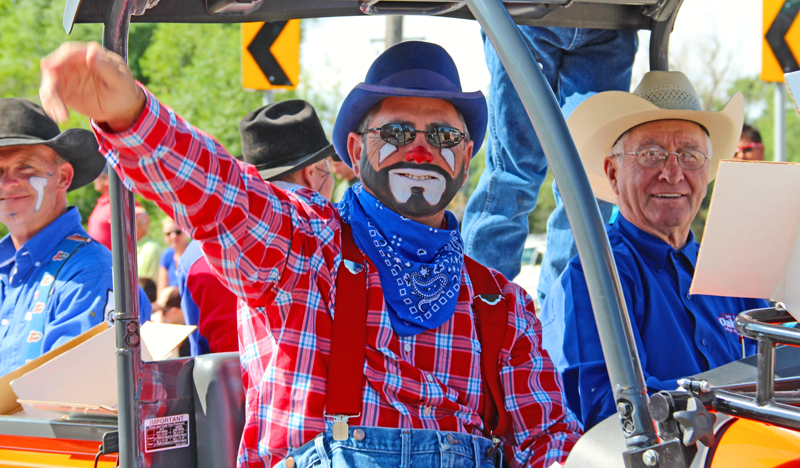 A rodeo clown waves to the crowd during the parade at the 2012 Fourth of July Independence Celebration. To his left is Ken Woolstenhulme, a former mayor of Oakley.