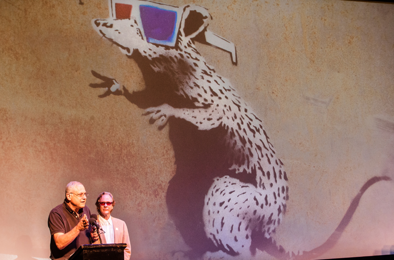 "Java Cow owner Ken Davis, left, and Egyptian Theatre Manager Randy Barton discuss the ""Save Our Banksy"" fundraiser during a press conference Tuesday, at the Egyptian Theatre. The Banksy ""Dirty Rat"" street art was painted on a stage door in January 2010 during a Sundance Film Festival"