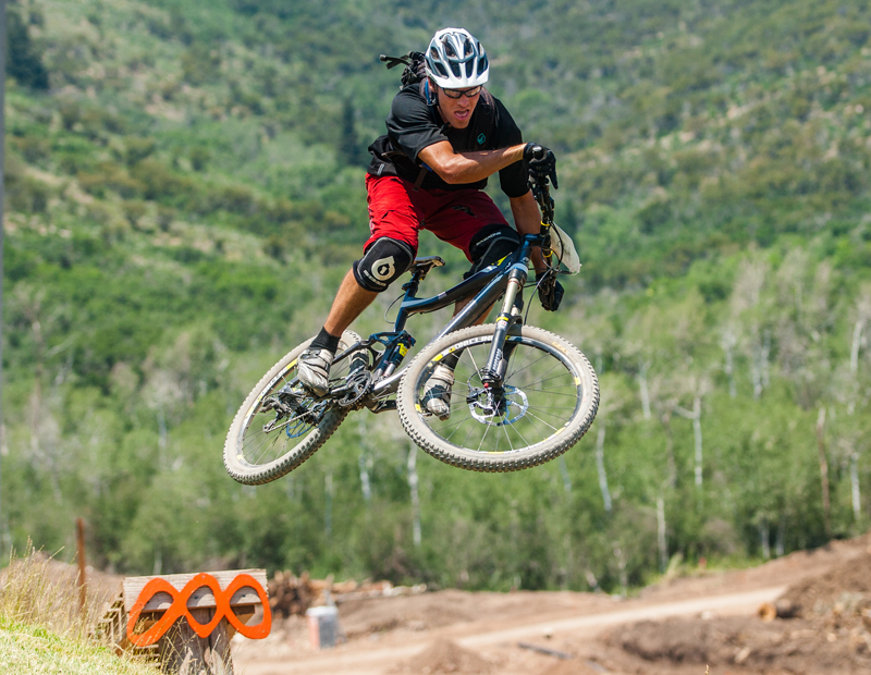 Tyler McQueen takes flight off a wooden ramp just before crossing the finish line at the Scott Enduro Cup race, presented by GoPro, Saturday, July 19, at Canyons Resort. Photo by Christopher Reeves/The Park Record.