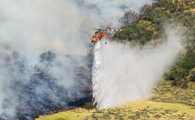 An Aircrane Helitanker returns after filling with water from Rockport Reservoir and carries it to dump on the perimeter of the fire Friday, July 25 at Rockport Estates. (Christopher Reeves/Park Record)