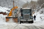 A large snow-blowing machine deposits snow into a dump truck on Daly Avenue Thursday morning as part of a Public Utilities Department hauling operation. The snow is taken out of the tightly packed neighborhood in an effort to ensure streets are passable.