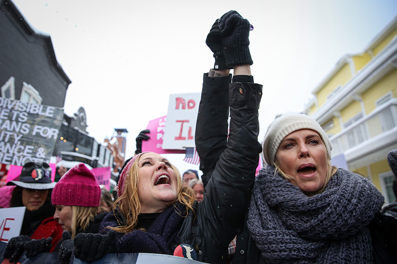"Mary McCormack, left, holds hands with Charlize Theron, right, as they chant ""Love, not hate, makes America great!"" while walking down Main Street during the March on Main Saturday morning, Jan. 21, 2017. More than 5,000 people turned up for the march despite the snowy and 20-degree conditions. (Tanzi Propst/Park Record)"