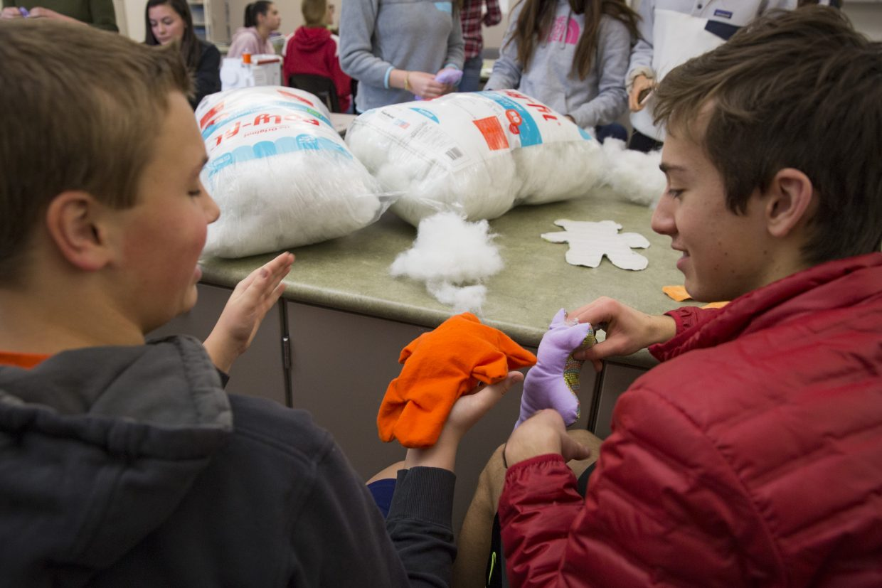 Jonathan Clifton, left, and Nick Moss, right, stuff their Dolls of Hope teddy bears with stuffing during the Future Business Leaders of America service event on Saturday, January 13, 2018. The dolls, once finished, will be sent to refugee children. (Tanzi Propst/Park Record)