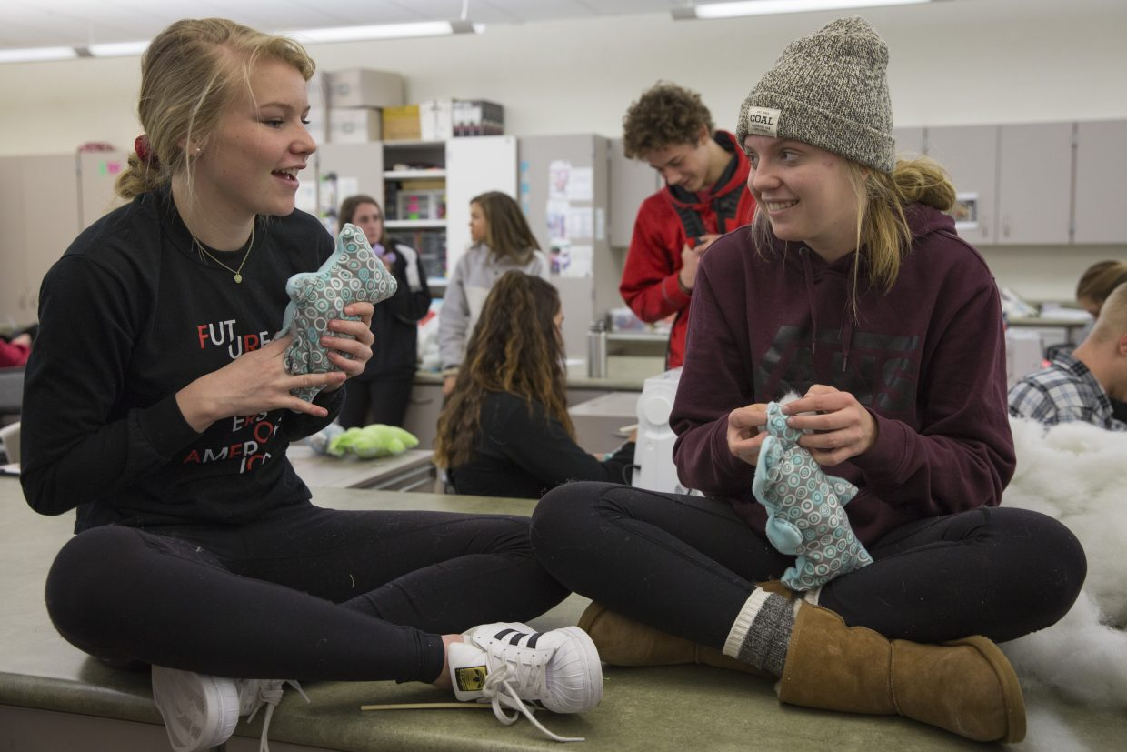 Haley Maki, left, and Charlotte Adams, right, converse while stuffing their Dolls of Hope teddy bears during the Future Business Leaders of America service event at Park City High School on Saturday, January 13, 2018. The dolls, once stitched, stuffed and sewn, will be sent to refugee children. (Tanzi Propst/Park Record)