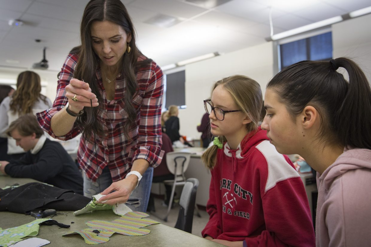 Sarah Parson, from left, demonstrates how to stitch eyes and a nose onto a Dolls of Hope teddy bear for Jaynie Glasmann and Kataleeya Powers during the Future Business Leaders of America service event at Park City High School on Jan. 13.