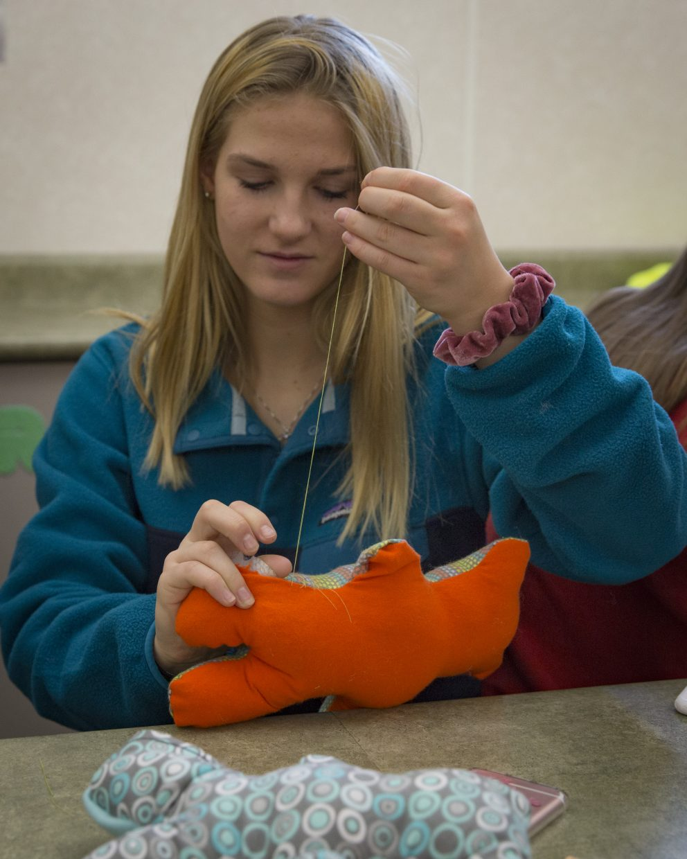 Jade Moffat, a Park City High School sophomore, stitches up the side of a handmade teddy bear during the Future Business Leaders of America's service event — Dolls of Hope — on Saturday, January 13, 2018. The event crafted the dolls to send to refugee kids. (Tanzi Propst/Park Record)