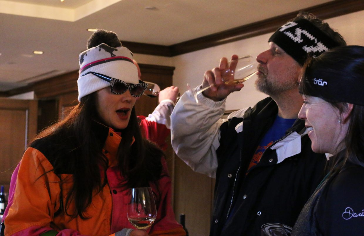 Kim Brown and Dennis Gaspari chat with a friend in their retro ski gear while at Wine on the Mountain, an event held on March 2, 2018 at Deer Valley Resort's St. Regis. The event benefitted the National Ability Center as part of its Red, White and Snow fundraising efforts. (Kira Hoffelmeyer/Park Record)