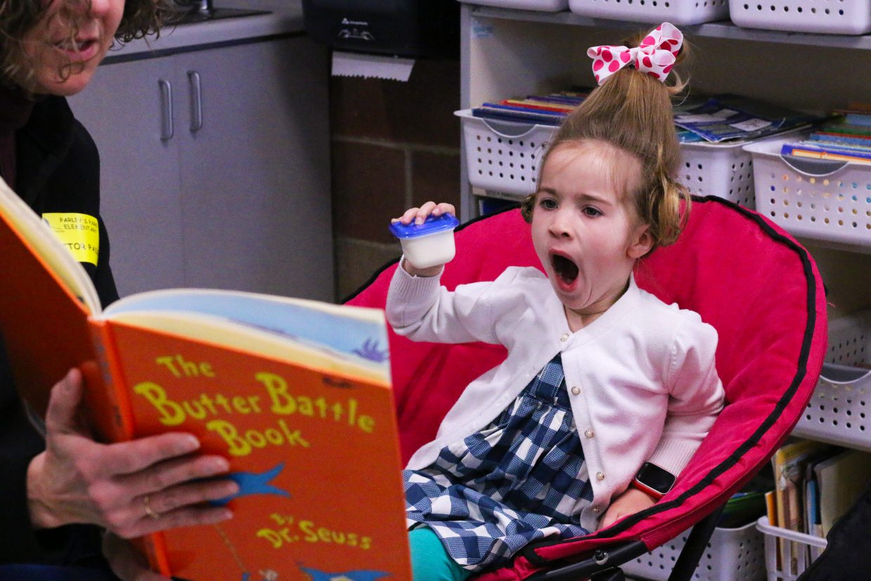 Olivia Hampton, a second grade student at Parley's Park Elementary School, yawns as volunteer Michelle Ascherl reads her a Dr. Seuss book. The school held a reading day in honor of the renown author's birthday and Read Across America Day on March 2, 2018. (Kira Hoffelmeyer/Park Record)
