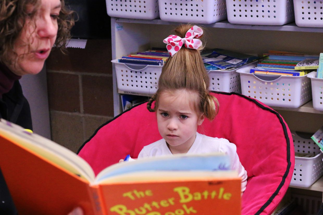 Second grader Olivia Hampton sits in her Cindy Lou Who-themed dress up while volunteer Michelle Ascherl reads to her. Parley's Park Elementary School brought in volunteers to read to students in honor of Dr. Seuss' birthday on March 2, 2018. (Kira Hoffelmeyer/Park Record)