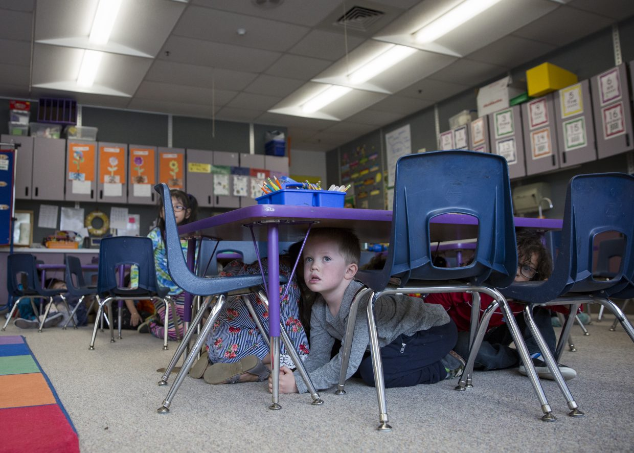 McPolin Elementary School kindergarteners huddle underneath a table as they participate in the Great Utah Shakeout earthquake drill Thursday morning, April 19, 2018. (Tanzi Propst/Park Record)
