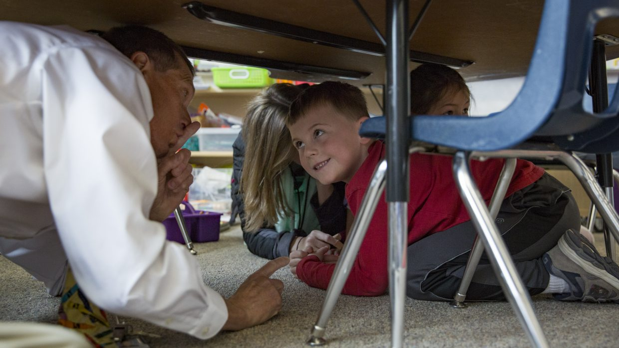 McPolin Elementary School Principal Bob Edmiston, left, tells kindergarteners to be quiet as they huddle underneath a table as they participate in the Great Utah Shakeout earthquake drill Thursday morning, April 19, 2018. (Tanzi Propst/Park Record)