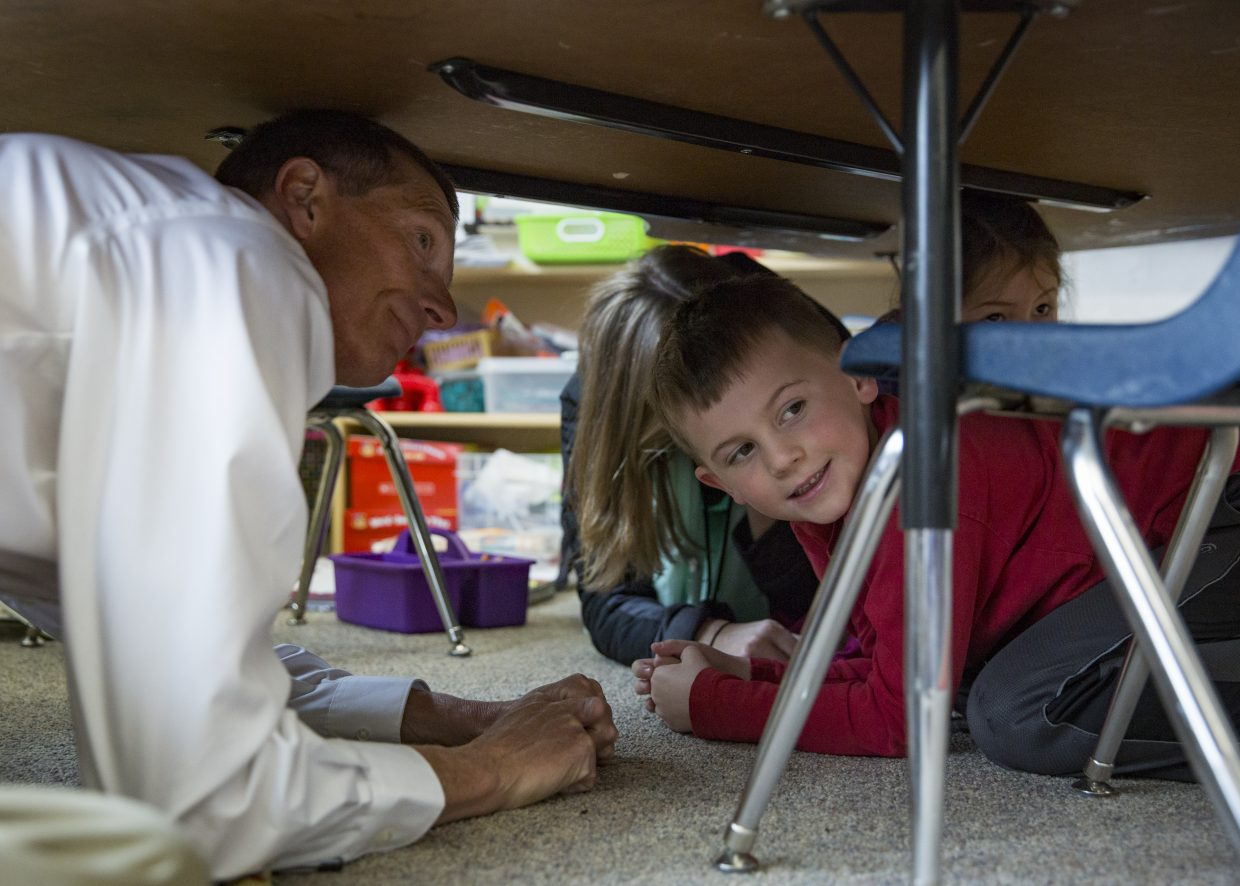 McPolin Elementary School Principal Bob Edmiston, left, huddles underneath a table with kindergarteners as they participate in the Great Utah Shakeout earthquake drill Thursday morning, April 19, 2018. (Tanzi Propst/Park Record)