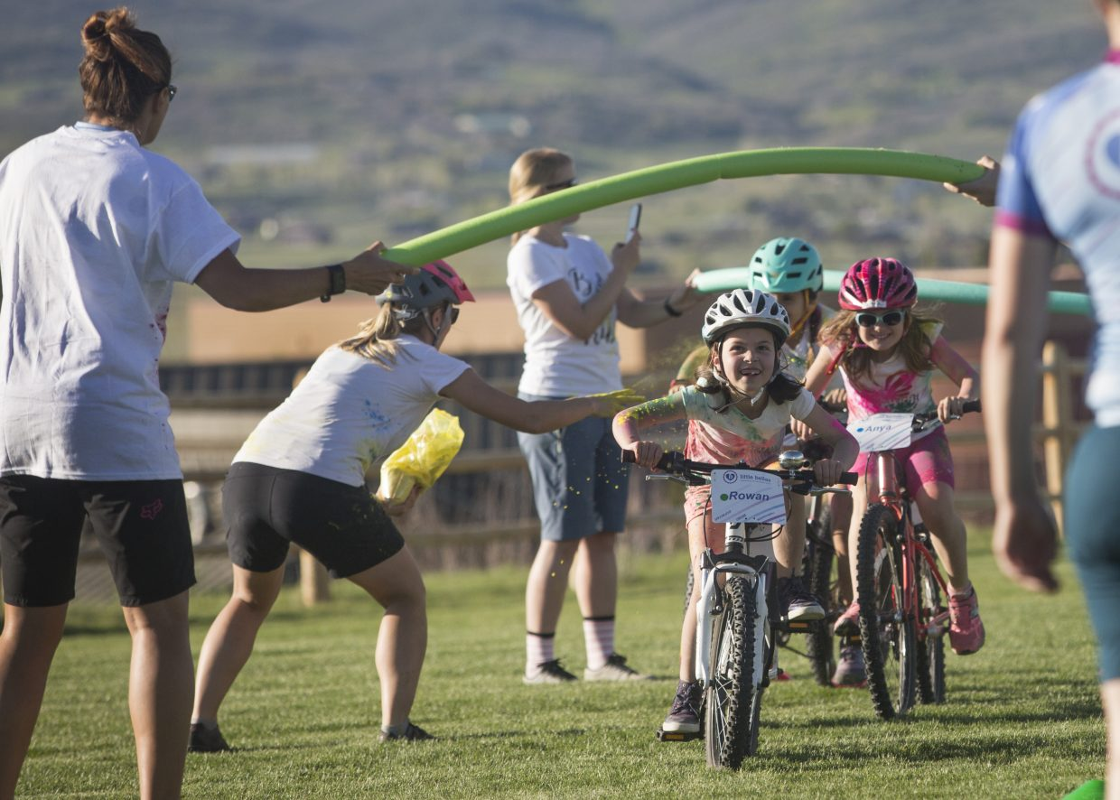 Rowan Davis, middle, is dusted with yellow color powder by Little Bellas Biking mentor Sam Mueller, second from left, as she ducks underneath a pool noodle during a biking exercise at Trailside Park Wednesday afternoon, May 16, 2018. The group was dusted in a variety of colors during their color day festivities. (Tanzi Propst/Park Record)