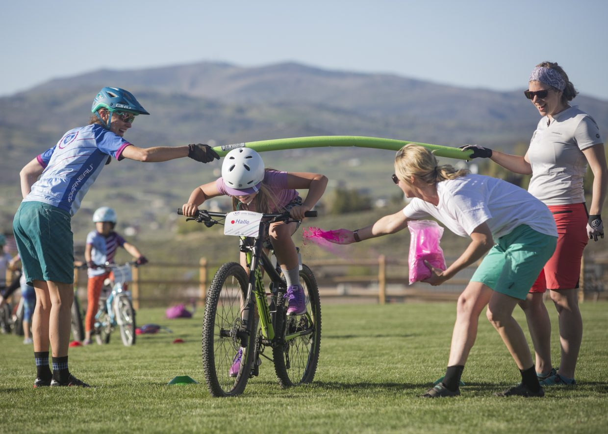 Halle Peterson, middle, is dusted with pink color powder by Little Bellas Biking mentor Kirsten Dale, right, as she ducks underneath a pool noodle during a biking exercise at Trailside Park Wednesday afternoon, May 16, 2018. (Tanzi Propst/Park Record)