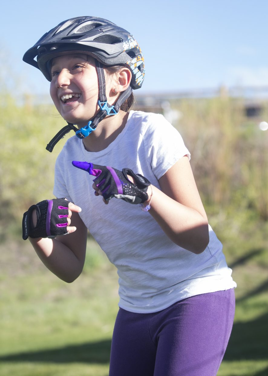 Nathalia Hurtado laughs after dipping her finger in a bag of purple color powder during the Little Biking Bellas color day festivities at Trailside Park Wednesday afternoon, May 16, 2018. The group was dusted in a variety of colors during their color day festivities. (Tanzi Propst/Park Record)