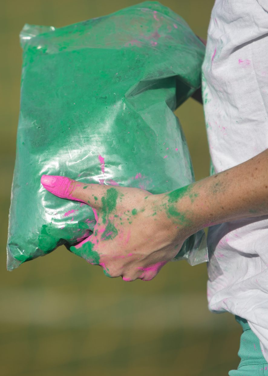 Kirsten Dale prepares to throw green color dust at Little Biking Bellas as they participate in the group's color day activities at Trailside Park Wednesday afternoon, May 16, 2018. The group was dusted in a variety of colors during their color day festivities. (Tanzi Propst/Park Record)